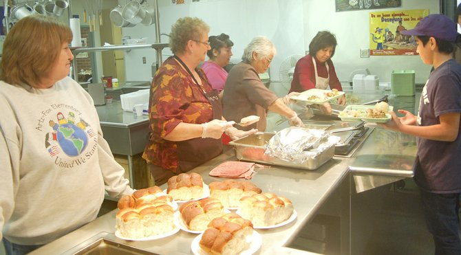 Mabton School District head cook Rhonda Hendricks (L) oversees the dishing up of food by her volunteers (L-R), former Mabton Mayor Vera Zavala, Council members Oping Hutson, Sophia Sotelo and Mabton School District Superintendent Minerva Morales.