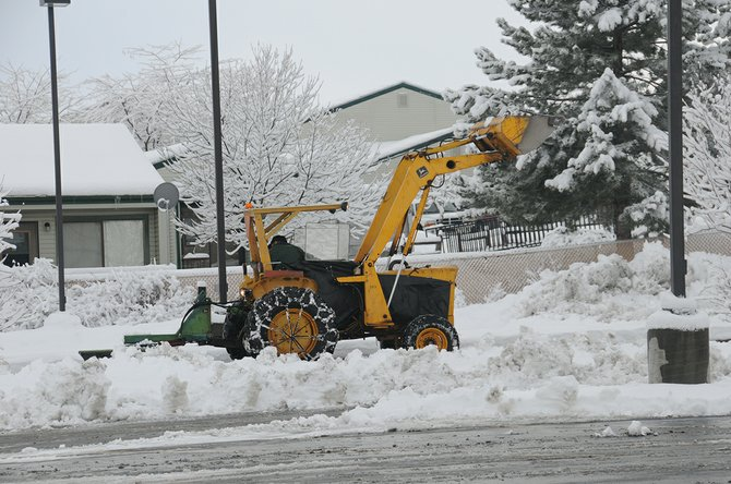 A backhoe cleans snow from a Grangeville parking lot following a 2010 snow event.