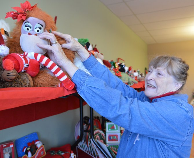 VOLUNTEER JUDY RILEY stocks the shelves of the Christmas décor shop, which also features cloth-ing and home accessories.