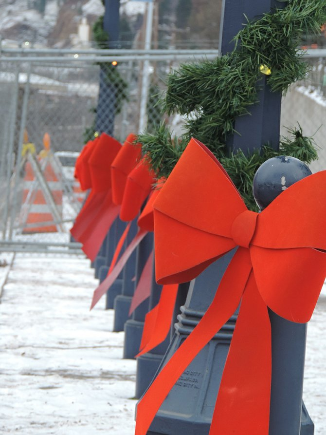 RED BOWS help set the stage for the annual lighting of the Christmas tree.