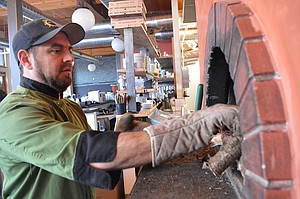 AARON BAUMHACKL, owner of Solstice Wood Fire Café, does a test run of the wood-fired pizza oven at the restaurant's new location on Portway Avenue down by the Hood River waterfront. The restau-rant move was made possible in part by a Kickstarter fundraising campaign.