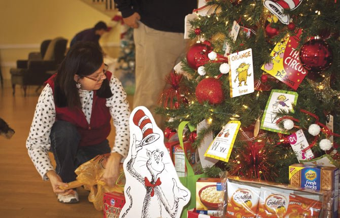 "Cindy McLean of the Mid-Columbia Health Foundation prepares to bag up the wealth of food, books and toys under the Dr. Seuss-themed  ""Reading Tree,"" donated to the Festival of Trees by XiZeta, Saturday at the Festival of Trees family day sponsored by Fred Meyer."