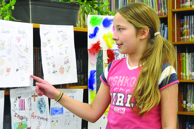 Grangeville Elementary Middle School student Rio Buck explains her PTA Reflections project at the Nov. 21 Reflections Gallery at the GEMS library.