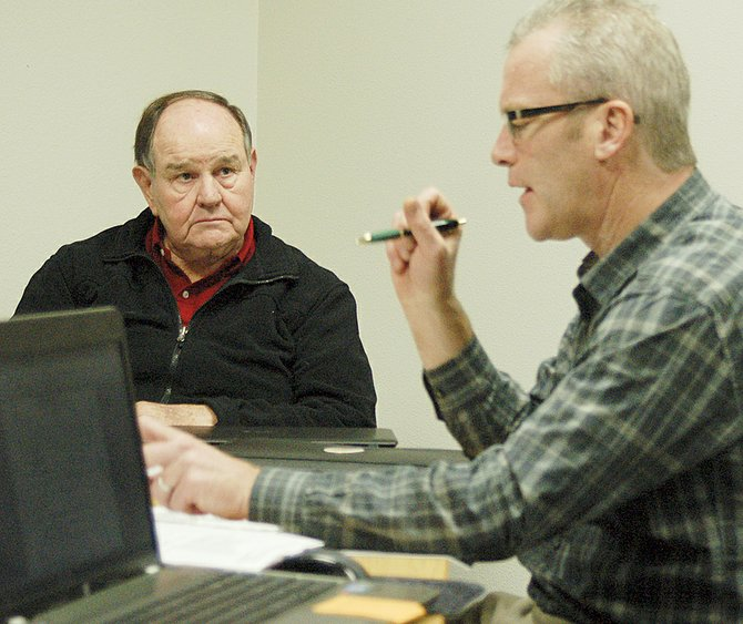 Grandview Port Commissioner Ron Grow listens as David McFadden, president of the Yakima County Development Association, reviews marketing plans for 2014.