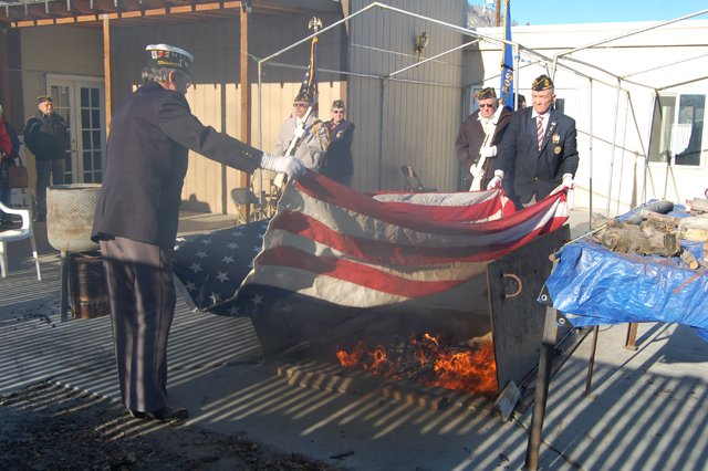 American Legion District 9 Commander Denny Pittman, left, and Columbia Post 97 member George Pearson, far right, lower a retired American flag over a fire Saturday at the Legion Hall, 102 N. Third St., Brewster. In the background, from left to right, are fellow Legion members Walt Peckham, Gale Nilsen, Sherilyn Jacobson and Ray Davis. Photo by Jennifer Marshall.