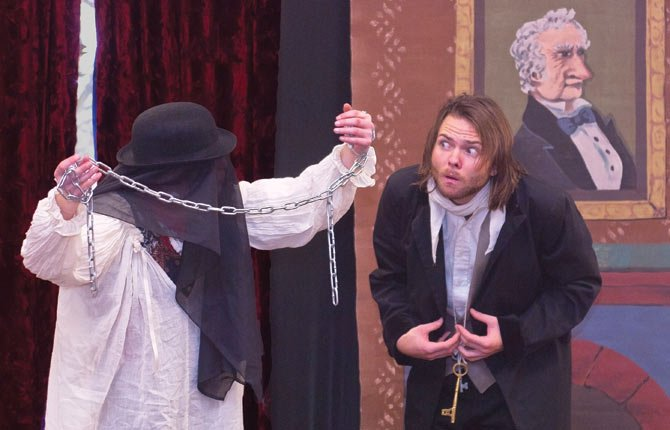 "Ebenezer Scrooge (Saumuel Munger), right, meets the ghost of his business partner Jacob Marley (Emily Robison) during a performance of ""A Christmas Carol."" The show was performed by the Traveling Lantern Theater Company at The Dalles Wasco County Library Dec. 12."