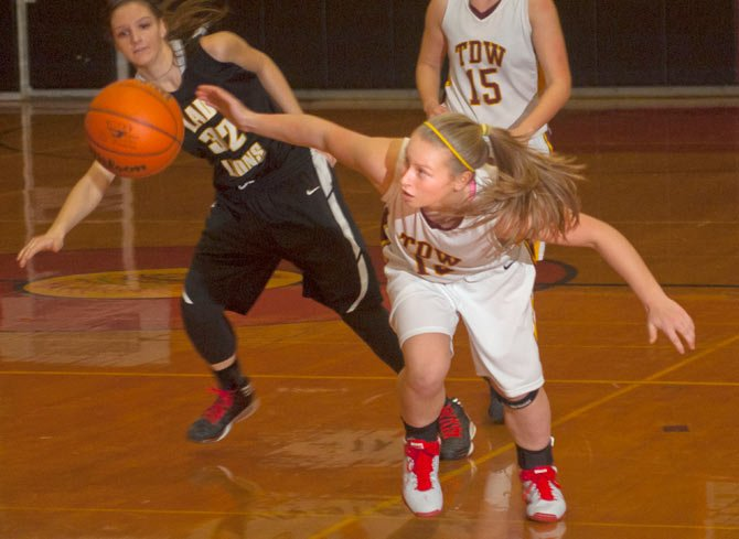 The Dalles Wahtonka freshman Sierra Watson, right, recovers the ball, slapped away by Saint Helens senior Brittney Bartolomucci during Friday's game in The Dalles. The Eagle Indian defense held the Lions to four field goals and rolled to an easy 35-11 victory in their home debut.