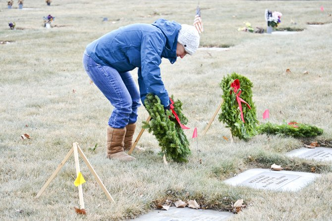 The third annual Wreaths Across America event in Grandview last Saturday was held in conjunction with a national ceremony to place wreaths at the graves of all military veterans. Inset Ginger Emerson, whose son died while serving in Iraq, spoke to the crowd. After the ceremony, wreaths were placed at the grave sites of about 400 local veterans at the Grandview cemetery. Local students and volunteers helped with the effort, such as Cathlin Schmitke from the Walmart Distribution Center in Grandview (above).