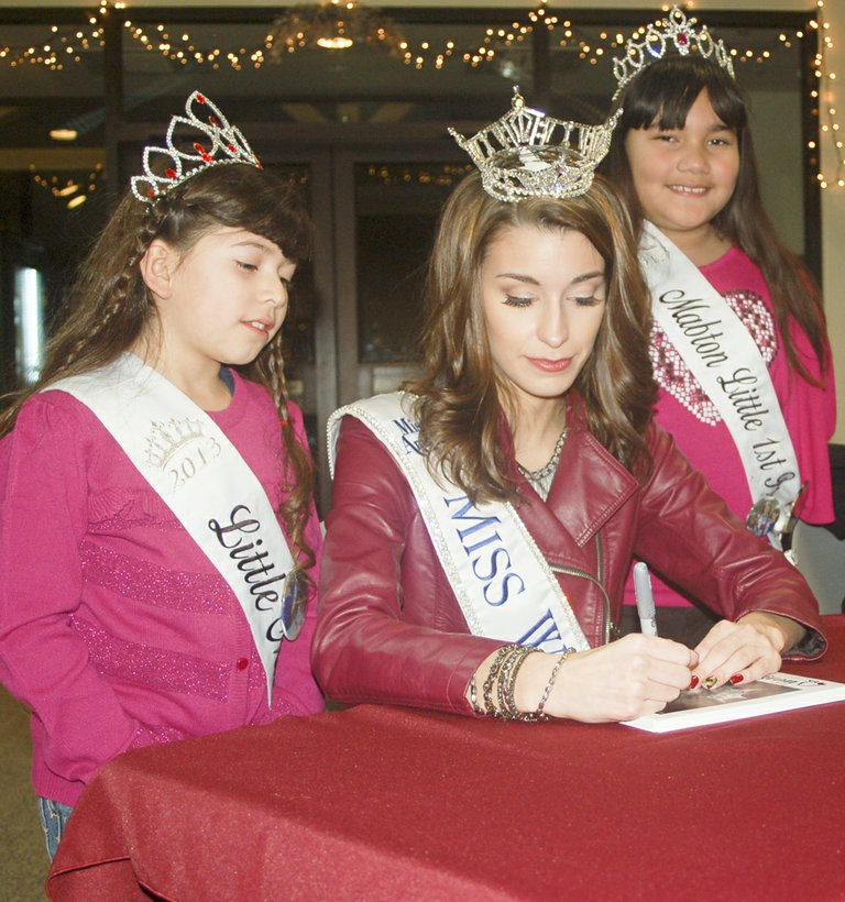 Little Miss Mabton Jessalyn Jalifi (L) spells her name for reigning Miss Washington Reina Almon, who took time to sign autographs for those attending a reception held in Almon's honor last night at the Sunnyside Community Center. Also pictured is Little Miss Mabton First Princess Lily Villa.