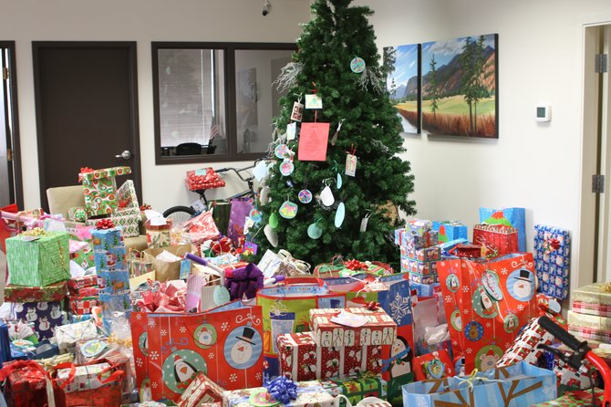 Presents for indigent families surround the sharing tree at North Cascades Bank in Omak.