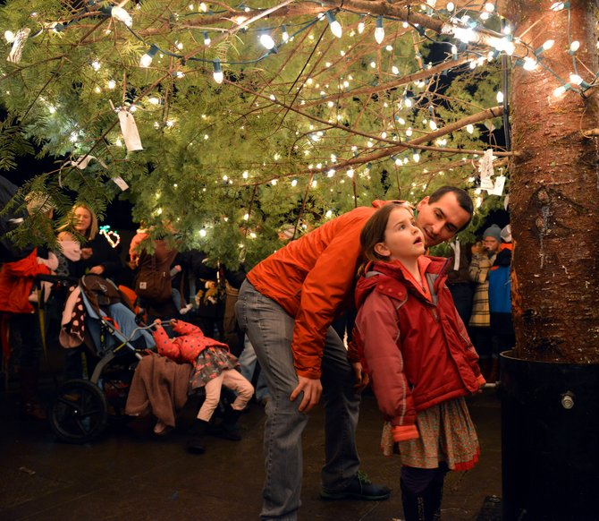 "Hazel Haspela and her father, Kevin, share a moment beneath the bright lights of the downtown Christmas tree Friday at Second and State streets. Several hundred people turned out to see the lights, and greet Santa Claus. The parade and tree lighting had been postponed one week after the snowfall on Dec. 6. ""It was great to see the community come together,"" Chamber Executive Director Mike Glover said. ""We really appreciate the city's efforts to get the street ready and providing vehicles for the parade."" The crowd went through three ""false starts"" in the light countdown, as contractor Hollywood Lights worked to connect the power at the scheduled 7 p.m."