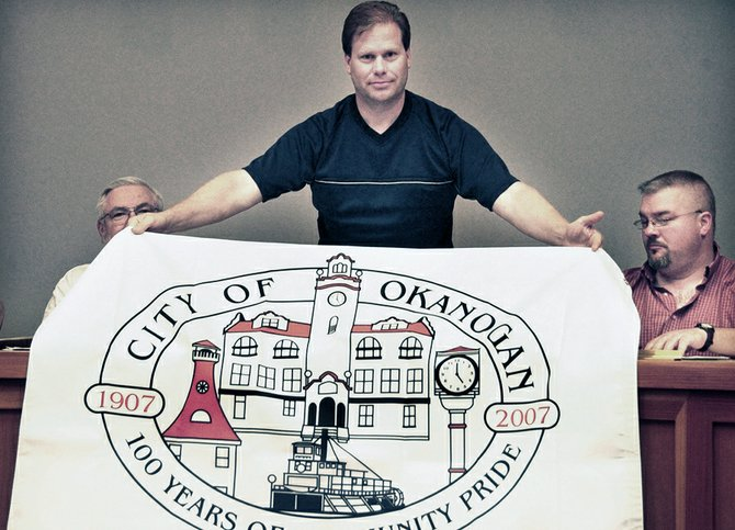 Michael Blake unveils the city of Okanogan's logo.