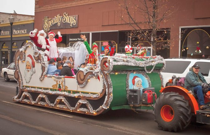 SANTA CLAUS, with his wife, a few elves and visitors, is driven down Third Street Saturday by Gary Honald, who gave sleigh rides in downtown The Dalles. Dec. 21 is the last day to enjoy the downtown Santa and sleigh.