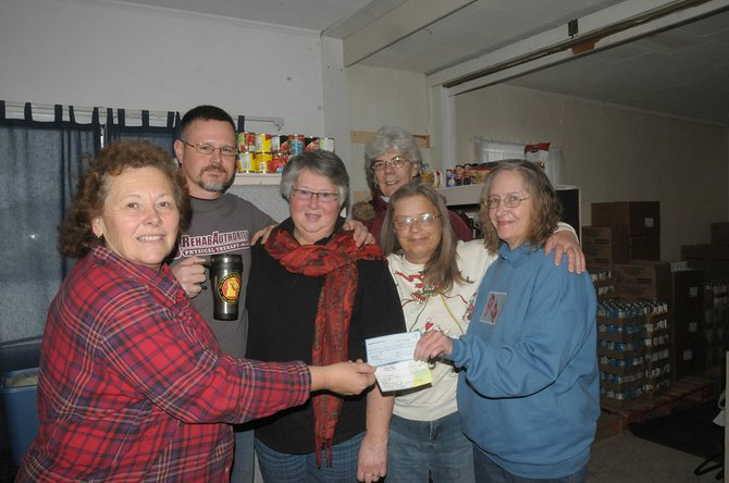 Grangeville's People First group recently held a memorial dinner for former member Cathy Sokolowski. They were able to raise and donate $765 to the Camas Prairie Food Bank last Friday, Dec. 13. Pictured here are (L-R) Carlene Whitesell, food bank manager, Troy Steinfort, Carol Schmidt and Nan Jensen (back), food bank volunteers and Jean Vavra and Robin Evans with People First.