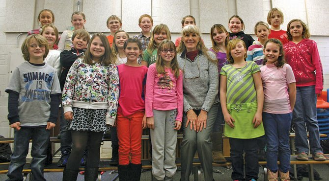 MUSIC TEACHER Margaret French poses with Dufur School fourth graders Dec. 17. French returned to the school where she taught for years to lead the winter program, coming up Thursday, Dec. 19, at 7 p.m.