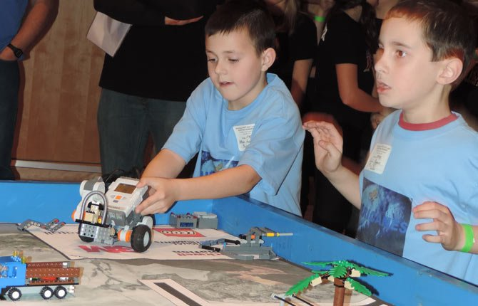 Ethan Pope, right, shows his excitement as Caleb Parsons readies their robot for the next part of the table course; both are fourth-graders with Col Wright robotics team.