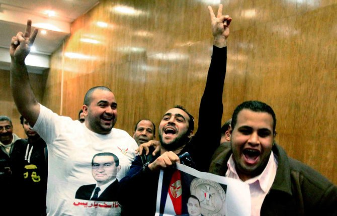 Egyptian supporters of former leader Hosni Mubarak celebrate after a court acquitted Mubarak's two sons and his last prime minister of corruption charges, judiciary officials said at a court, in Cairo, Egypt, Thursday, Dec. 19.