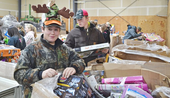 Blake Van Belle sports a reindeer cap he discovered in a bin as he sorts through donated toys at the Yakima Union Gospel Mission last Tuesday. A Sunnyside Christian High School student, he and his peers visited the mission to help sort donated toys, stock inventory in the mission gift shop and even performed a few yard clean-up chores. Also pictured is Ryan Roedel.