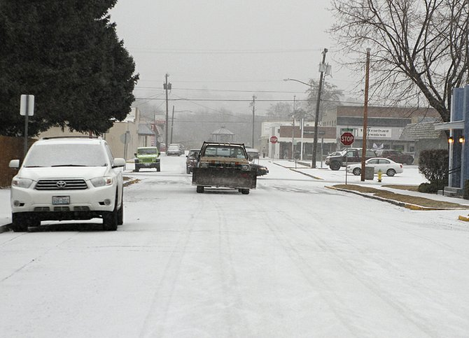 A truck with a snow plow on the front drives down Apple Avenue in Omak on Friday afternoon.