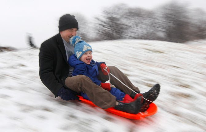 Matt Redmond, 3, and his father, Mike, ride a sled down a hill in Baltimore, Md. According to a government survey the detached dad is mostly a myth.