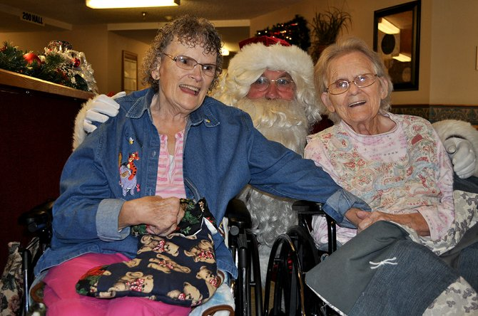 Santa Claus paid an early visit to Grangeville Health and Rehab last Thursday, Dec. 19, to pass out gifts homemade by NICI inmates. Among the recipients were residents (L-R) Brenda Childers and Ruth Whitesell.