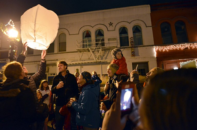 CROWD WATCHES as a Chinese lantern is illuminated just before release on Dec. 13, shortly after the tree lighting ceremony. The lanterns are classified as pyrotechnics and require a licensed handler.