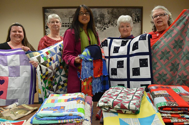 TWENTY QUILTS made by five ladies in Cascade Locks will be donated to Helping Hands Against Do-mestic Violence. From left to right are Jill Rodabaugh, Pat Power, Helping Hands Executive Director Lee Montavon, Sharon Dean, and Sherilyn Foley. All are holding up examples of the quilts they made. Not pictured is Jean Hankel, who made the quilt Montavon is holding.