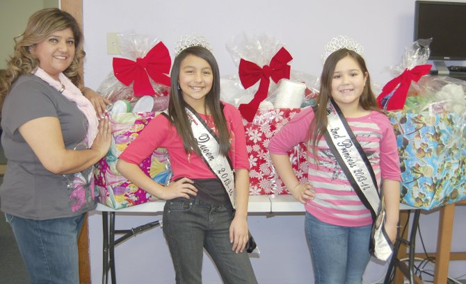 The Panda Bear Daycare Court visited Sunnyside's Lower Valley Crisis and Support Services yesterday (Monday) loaded with boxes of toys, food and clothing to cheer up needy families using the center's services this holiday season. Pictured are (L-R) domestic violence advocate Rosalinda Alvarez, and Panda Bear Court Queen Nevaeh Palomarez and Second Princess Keiana Haskinson-Palomarez.