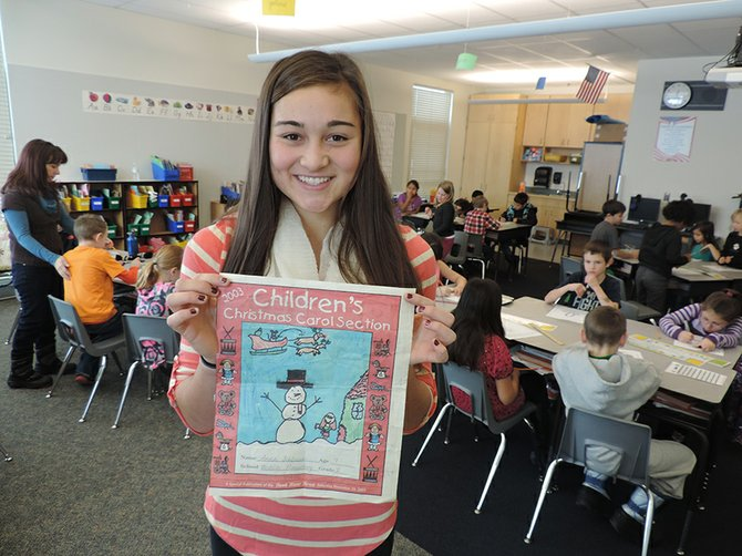 HRVHS senior Anna Schlosser holds her 2003 drawing during her visit to Joella Rockett's second-grade class at Westside Elementary.