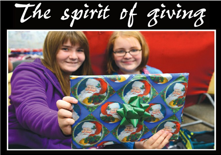 "TAYLOR BEAM and Emma Buckwalter, top, hold a newly wrapped present in the ""Operation Make A Difference"" project."