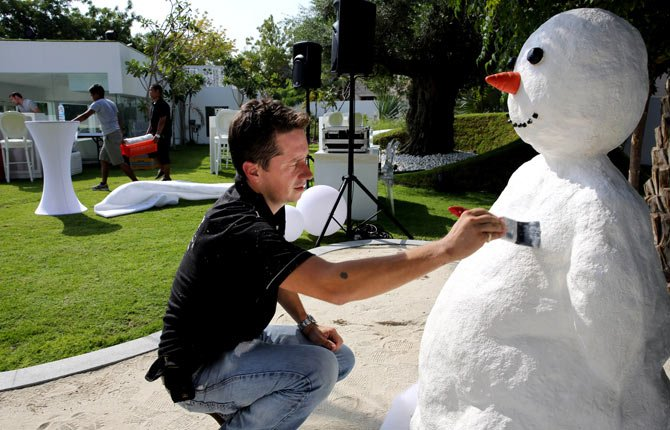 BEN ELLIOTT-SCOTT of Desert Snow company, a company which specializes in artificial snow, works on a snowman, a few hours ahead of a Christmas party Dec. 21 at a private villa, in Dubai, United Arab Emirates. The Middle East's brashest city is increasingly embracing the trappings of Christmas in a way that would be unthinkable in more conservative parts of the Muslim world. Christmas trees adorn shopping centers and residential neighborhoods, and high-end hotels try to outdo one another with extravagant and boozy holiday dinners.