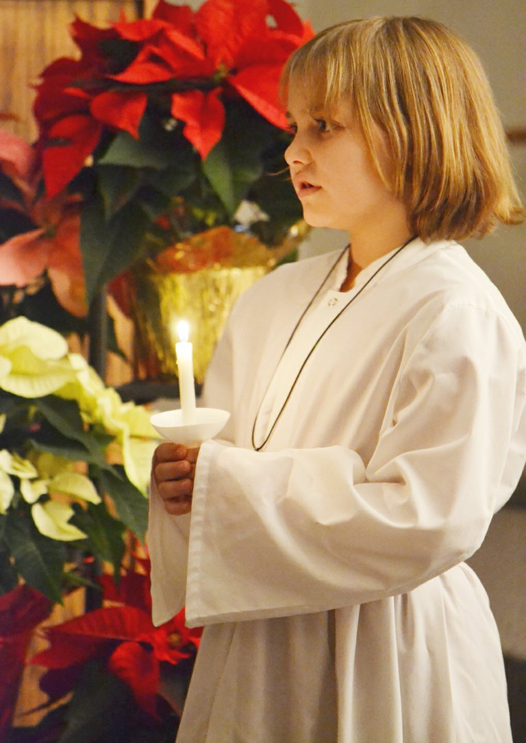 The Christmas Eve service at Our Saviour's Evangelical Lutheran Church in Sunnyside this past Tuesday night concluded with a candle lit ceremony. Pictured helping with the event is young acolyte Olivia Mears.