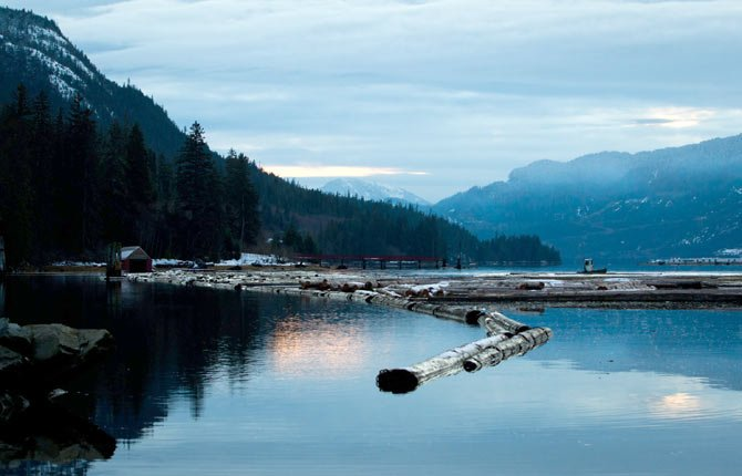A WORKER uses a small boat to move logs on the Douglas Channel at dusk in Kitamaat, British Columbia, Canada. Douglas Channel is the proposed termination point for an oil pipeline from Alberta as part of the Enbridge Northern Gateway Project. A review panel recommended Dec. 19 to the Canadian government approve a proposed pipeline to the Pacific Coast that would allow Canada's oil to be shipped to Asia.