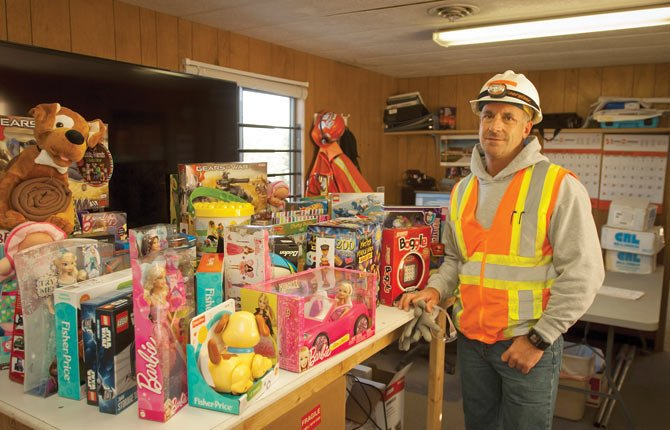 GREG GARSKE, superintendent of Hoffman Construction, stands next to a table of gifts donated by contractors and subcontractors building the new Fort Dalles Readiness Center in The Dalles. The toys were donated to the local Salvation Army for distribution to area families. The company contributed more than 2,000 toys statewide to provide holiday cheer for families struggling through tough times.