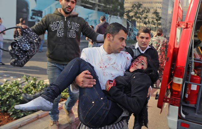 A Lebanese man carries an injured woman at the scene of an explosion in Beirut, Lebanon, Friday, Dec. 27. A strong explosion has shaken the Lebanese capital, sending black smoke billowing from the center of Beirut. The blast went off a few hundred meters (yards) from the government headquarters and parliament building.