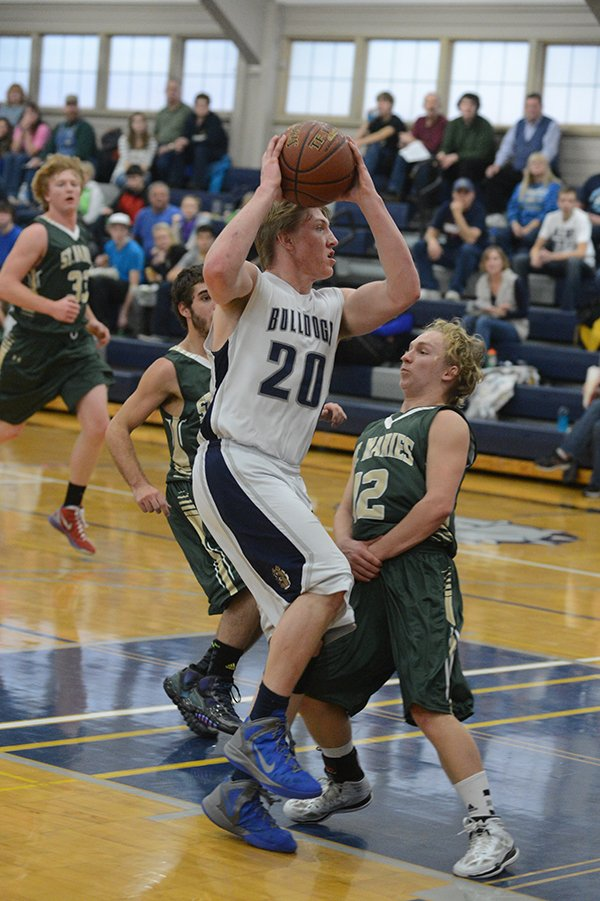 Guard Michael Wilson attacks the basket to score a layup as St. Maries' Jordan Bedwell shuffles his feet during Grangeville's Central Idaho League opener. Wilson drew at least six fouls in the game, and,  adding six-of-nine free throws, he co-led the Bulldogs with eight points last Saturday, Dec. 21.