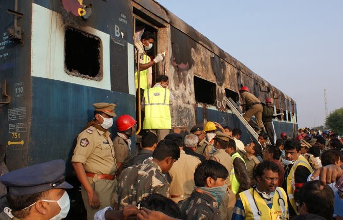 Policeman and firefighters search for victims of a train accident at Kothacheruvu, about 155 kilometers north of Bangalore, India Dec. 28. A fire engulfed two coaches of an express train in southern India early Saturday, killing at least two dozen, many of whom became trapped and suffocated after the doors failed to open, officials said.