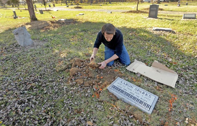 Aaron Pritchard replaces grass after laying a headstone on the previously unmarked grave of blues musician Aaron Sparks in Crestwood, Mo.