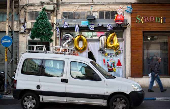 A man walks past a shop selling decorations ahead of New Years Eve in Tel Aviv, Israel Dec, 30. In Israel, the somber, soul-searching and autumnal new year of the lunar Jewish calendar overshadows the Gregorian's Jan. 1.