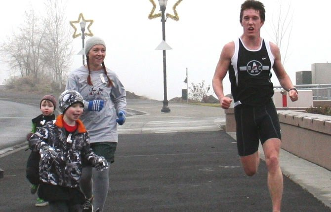 FORMER state champion harrier Alex Dillard, right, carves up the pavement at the Freeze Your Gizzards Blizzard run. In his 10k try, Dillard notched first place with a final time of thirty minutes and 28 seconds.
