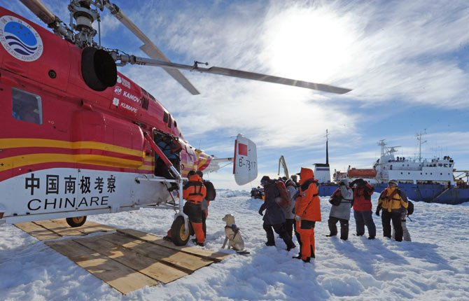 Passengers from the trapped Russian vessel MV Akademik Shokalskiy, seen at right, prepare to board the Chinese helicopter Xueying 12 in the Antarctic Jan. 2.