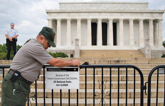 A National Park Service employee posts a sign on a barricade closing access to the Lincoln Memorial in Washington in October 2013. About half of Americans expect 2014 to be a better year than 2013.