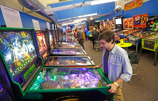 JOSH SAITELBACH plays pinball Dec. 16 on an 1998 Godzilla machine as he visits the Seattle Pinball Museum in Seattle, Wash. The museum allows visitors who pay the admission fee to play unlimited rounds on the machines, which range from the 1960s to modern-day games.