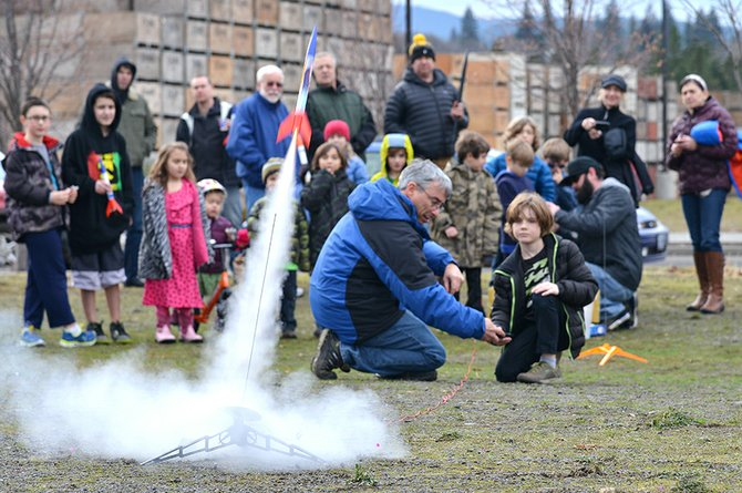 Watching the rockets: Gus Londin watches a rocket in dramatic takeoff during the annual New Year's Eve rocket launch, aided by teacher Zed Ruhlen of Hood River Hobbies. It was the final stage of the Dec. 31 rocket-making class. About 25 people gathered at Lot 1 on Hood River waterfront to watch rockets flash into the sky.