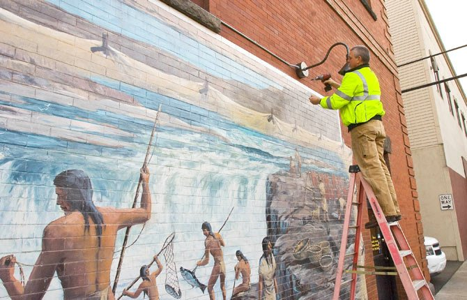 HARLEY FORK, an electrician with Hire Electric, mounts the last of six lights that will soon illuminate this Federal Street mural downtown The Dalles. Lights are currently planned for all four of the murals along Federal. See more about project, A2.