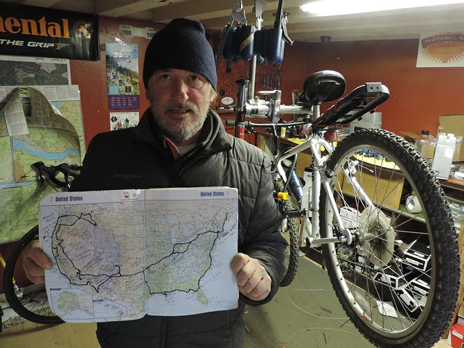 STEPHEN SWIFT displays the U.S. map of his travels in the past 21 months, while his bike is repaired at Mountain View Cycles.