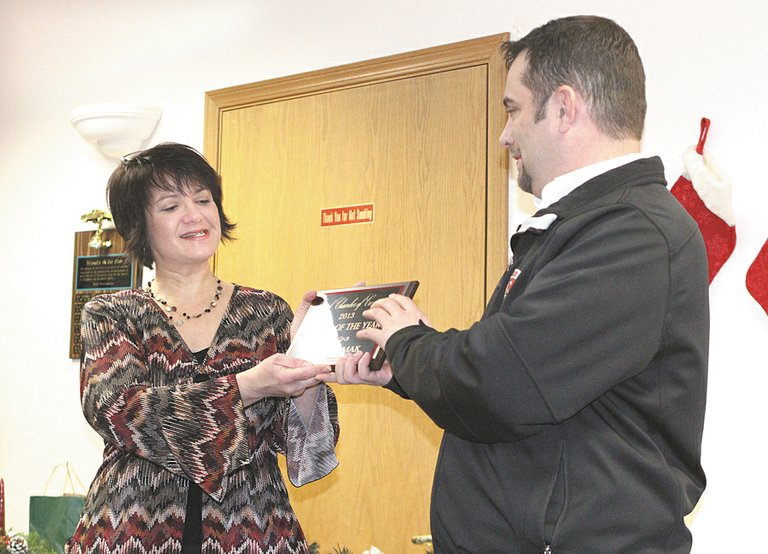 Omak Chamber of Commerce President Corina Radford, left, gives Big R store manager Andy Keith the Business of the Year Award on Wednesday afternoon.
