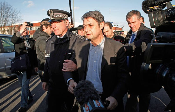 Goodyear's human resources chief, Bernard Glesser, center, and the firm's production manager Michel Dheilly, center right, leave the Goodyear plant in Amiens, northern France, Tuesday, Jan. 7. Two Goodyear managers held captive by angry French workers were freed Tuesday after police intervened, ending two days of standoff over the factory's bleak future.