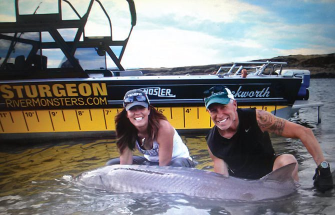 "JANA WALKER, host of ""Skullbound TV,"" poses with fisherman Greg Gustafson and a sturgeon caught during filming in The Dalles. The episode airs Wednesday and will feature an even larger catch.	Contributed photo"