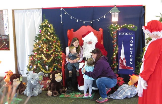 SANTA VISITS with children on a Saturday before Christmas. This family was among 350 children and their parents who visited Mr. and Mrs. Claus at the old Griffith Motors showroom.	Contributed photo